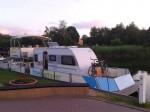 freecamper mit Wohnwagen in der Abendsonne vor Burgwall